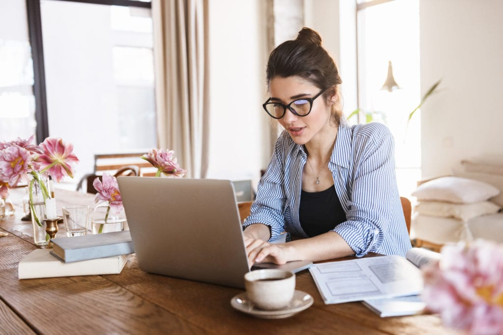 Image of lovely pretty woman typing on laptop while working or studying at home